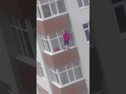 Bebaimė moteriškė valo langus penktame aukšte