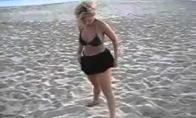 Girta blondinė mėgaujasi jūra ir vėju