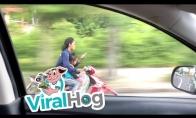 Važiuoja motociklu su vaiku ir rašo žinutę